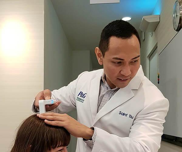 Saint Tiu, P&G Hair Care Senior Scientist demonstrating the hair tool